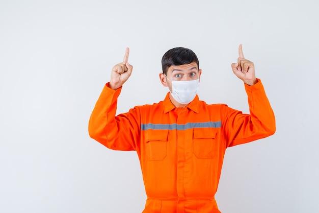 Homem industrial de uniforme, máscara apontando os dedos para cima e olhando curioso, vista frontal.