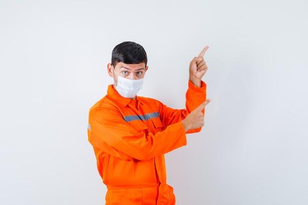 Homem industrial de uniforme, máscara apontando para o canto superior direito, vista frontal.