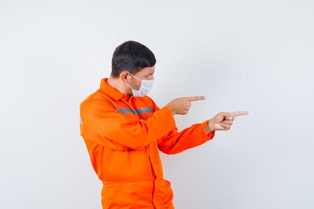Homem industrial de uniforme, máscara apontando para o lado e olhando com foco, vista frontal.