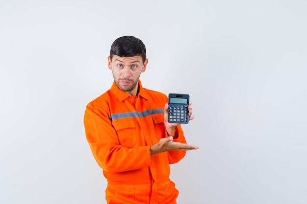 Homem industrial de uniforme, mostrando a calculadora e parecendo confiante, vista frontal.