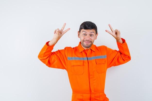 Homem industrial de uniforme, mostrando o sinal-v e olhando alegre, vista frontal.
