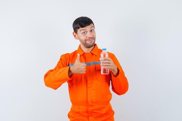 Homem industrial de uniforme segurando a garrafa de água, aparecendo o polegar e olhando alegre, vista frontal.