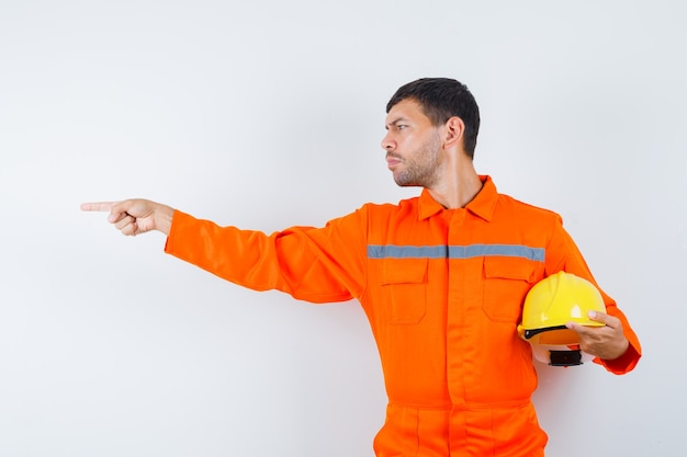 Homem industrial de uniforme segurando o capacete, apontando para o lado e olhando com foco, vista frontal.