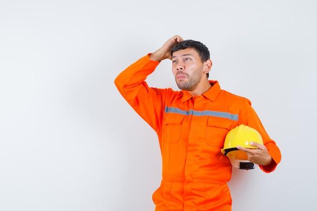 Homem industrial de uniforme segurando o capacete, coçando a cabeça e olhando pensativo, vista frontal.