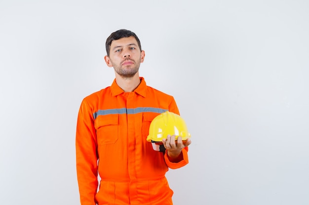 Homem industrial de uniforme segurando o capacete e parecendo calmo, vista frontal.