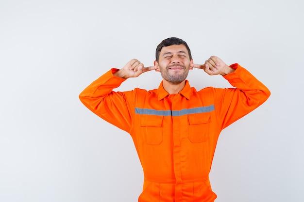 Homem industrial de uniforme tapando os ouvidos com os dedos e parecendo irritado, vista frontal.
