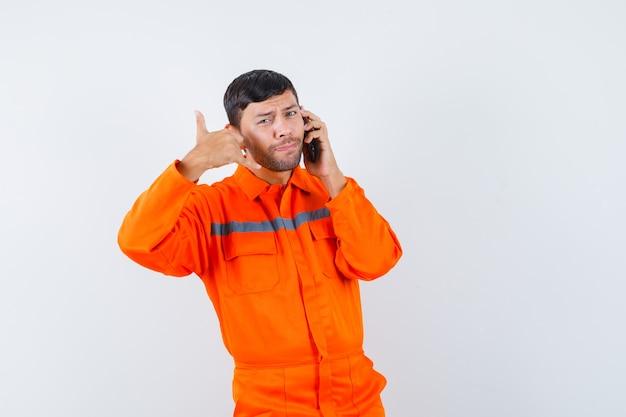 Homem industrial falando no celular com gesto de telefone em vista frontal uniforme.