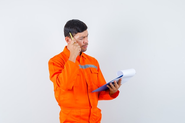 Homem industrial olhando para as notas na prancheta de uniforme e parecendo pensativo. vista frontal.