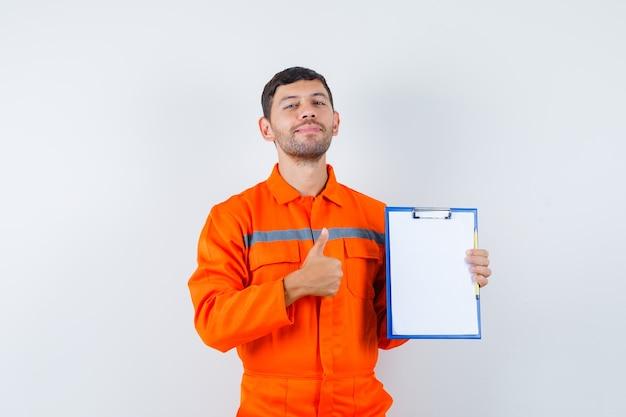 Homem industrial segurando a prancheta, aparecendo o polegar de uniforme e parecendo feliz, vista frontal.