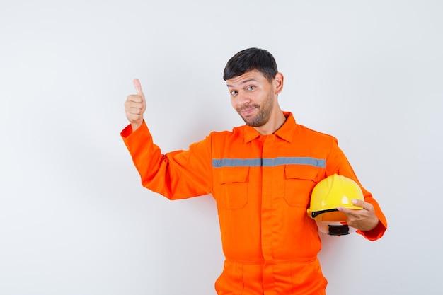 Homem industrial segurando o capacete, aparecendo o polegar de uniforme e parecendo alegre. vista frontal.