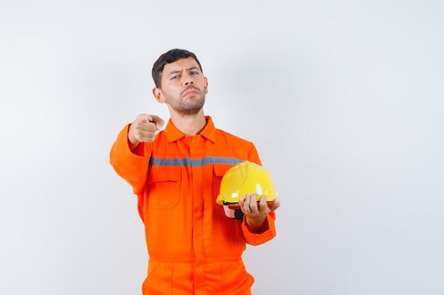 Homem industrial segurando o capacete, apontando de uniforme e parecendo confiante, vista frontal.