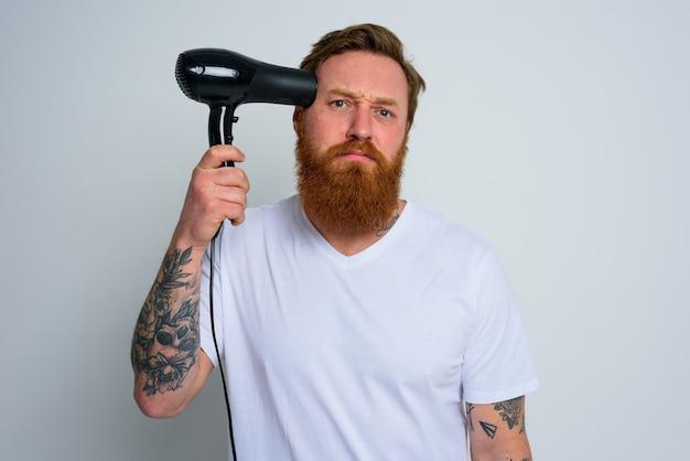 Homem infeliz com barba brincando com secadores de cabelo e uma arma de fogo