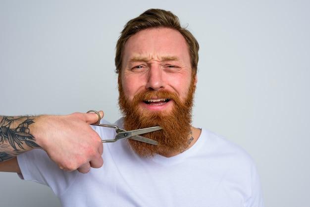 Homem infeliz com tesoura não quer cortar a barba