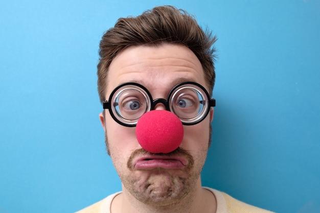 Homem infeliz com um nariz vermelho e óculos engraçados