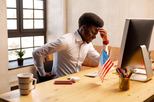 Homem infeliz e triste sentindo dor nas costas enquanto fica sentado demais no escritório