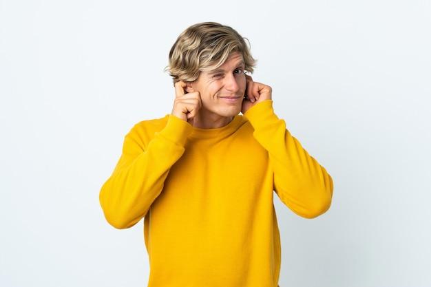 Homem inglês em uma parede branca isolada frustrado e cobrindo as orelhas