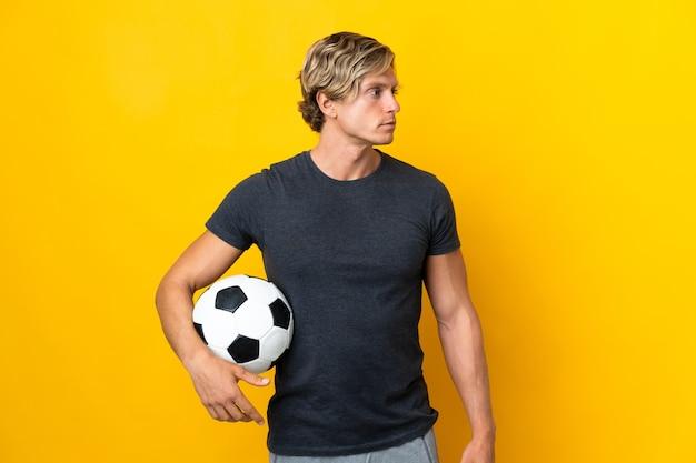 Homem inglês isolado amarelo com bola de futebol