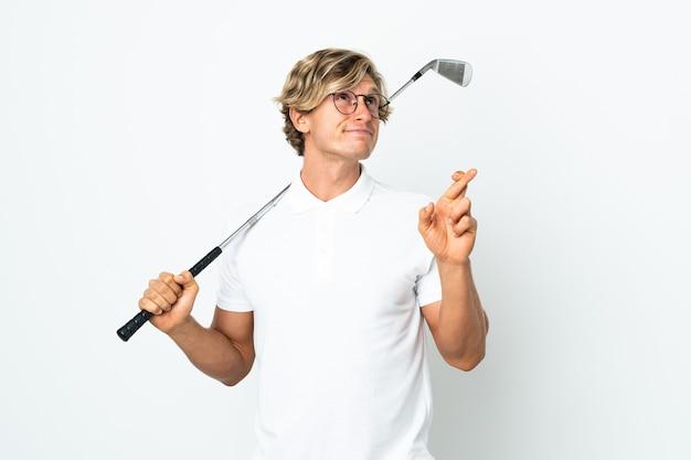 Homem inglês jogando golfe cruzando os dedos e desejando o melhor