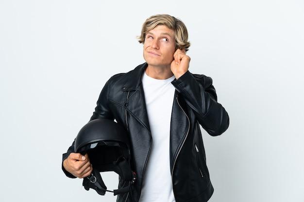 Homem inglês segurando um capacete de motociclista frustrado e cobrindo as orelhas
