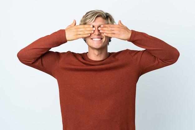 Homem inglês sobre fundo branco isolado cobrindo os olhos pelas mãos e sorrindo
