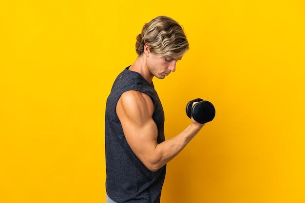 Homem inglês sobre isolado amarelo fazendo levantamento de peso