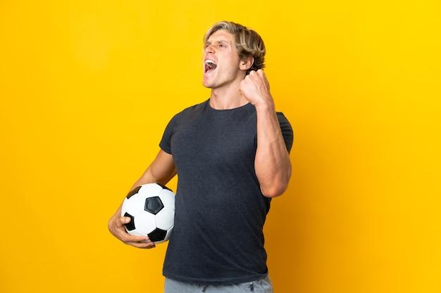 Homem inglês sobre parede amarela isolada com bola de futebol comemorando vitória