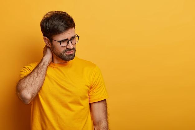 Homem insatisfeito e infeliz toca o pescoço, olha para algum lugar com expressão pensativa