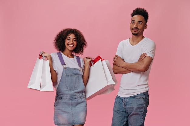 Homem insatisfeito esperando a namorada com sacolas de compras