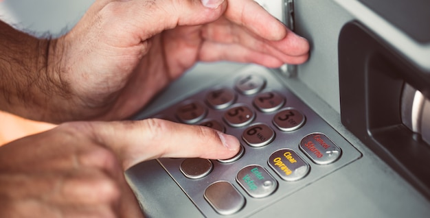 Homem inserindo um código pin para seu cartão de crédito em um caixa eletrônico, retirando dinheiro, conceito financeiro