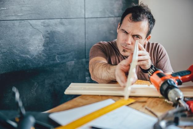 Homem inspecionando madeira