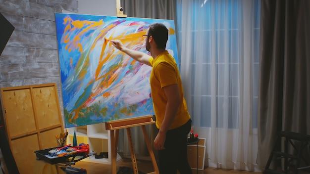 Homem inspirado ao pintar em uma tela grande no estúdio de arte.