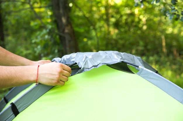 Homem instalando a barraca. material protegido da chuva. turismo ao ar livre. acampar na floresta.