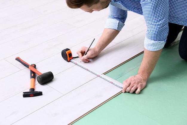 Homem instalando novo piso laminado de madeira