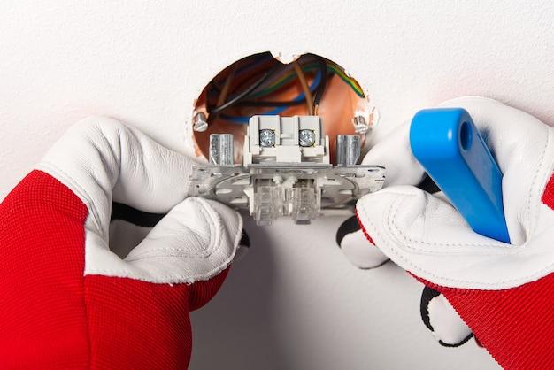Homem instalando o interruptor de luz após a renovação da casa. eletricista instalando interruptor de luz na parede pintada com chave de fenda
