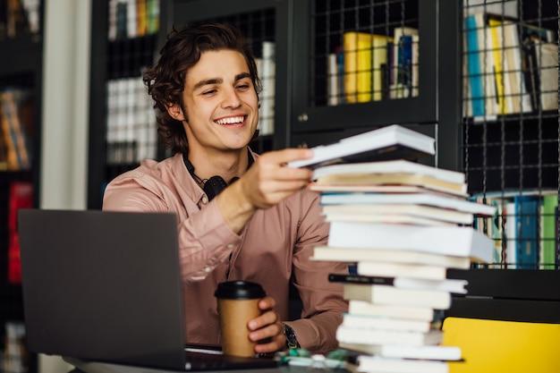 Homem intelectual lendo um livro sentado na biblioteca em frente a estantes com uma xícara de café nas mãos