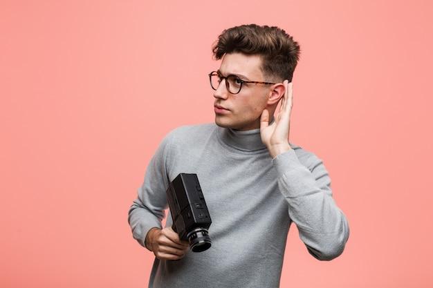 Homem intelectual novo que guarda uma câmera do filme que tenta escutar uma bisbolhetice.