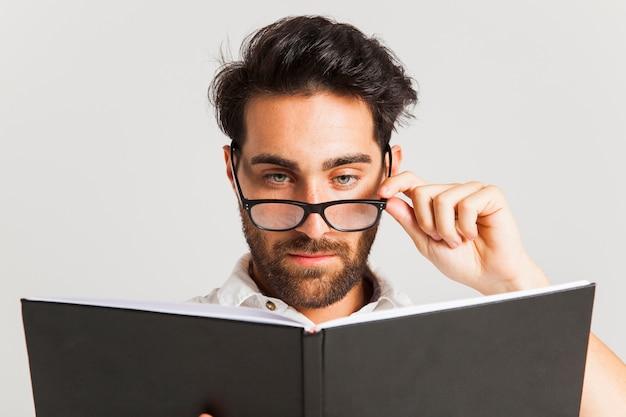 Homem intelectual posando com óculos e livro