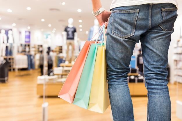 Homem inteligente com a sacola de compras na loja