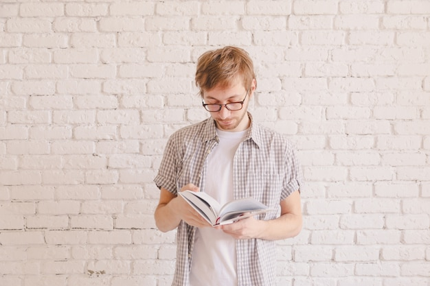 Homem inteligente com óculos, lendo um livro