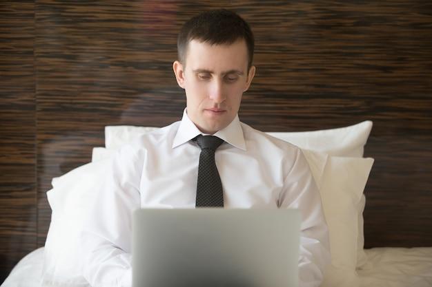 Homem inteligente deitado na cama digitando em um laptop Foto Premium