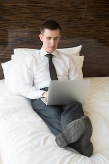 Homem inteligente deitado na cama digitando em um laptop