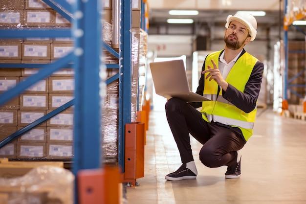 Homem inteligente e simpático segurando um laptop e contando caixas no depósito