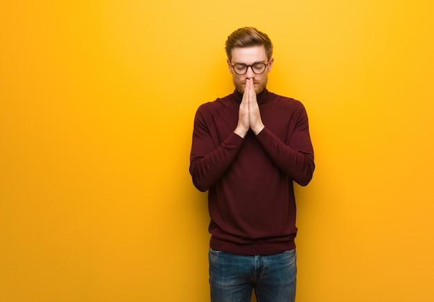 Homem inteligente jovem rezando muito feliz e confiante
