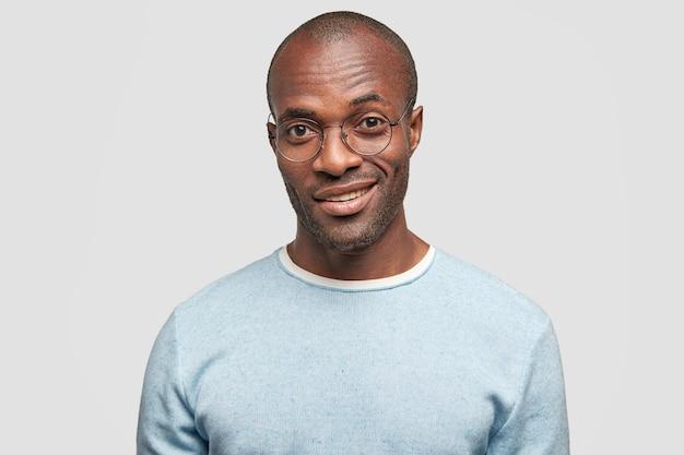 Homem inteligente modelo com sorriso gentil, tem aparência inteligente, tem certeza de seu sucesso, usa óculos redondos e suéter casual