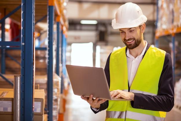 Homem inteligente positivo vestindo uniforme enquanto trabalhava como gerente de armazém