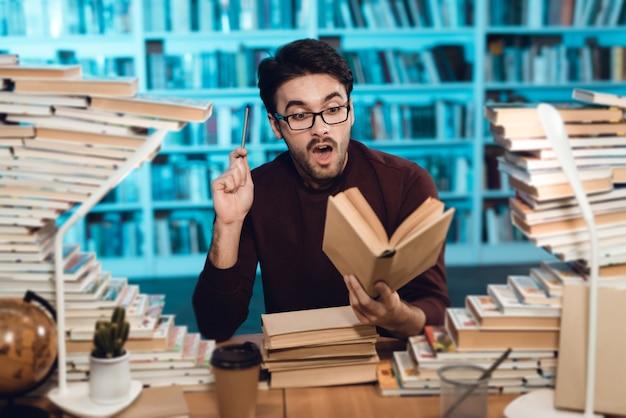 Homem inteligente, sentado à mesa, rodeado por livros na biblioteca