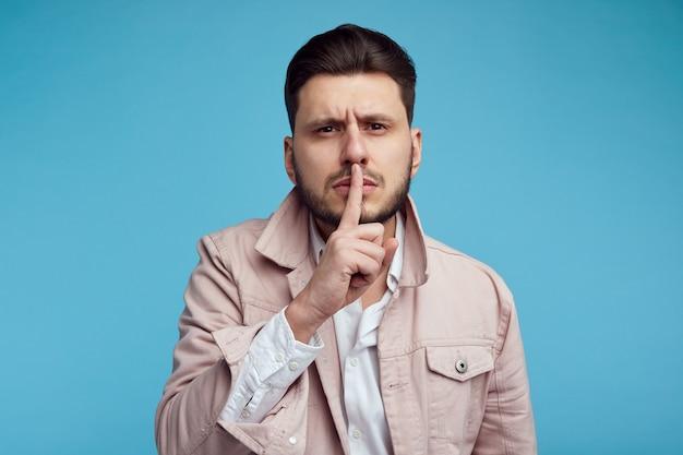 Homem intenso de aparência séria mostrando gesto de silêncio com o dedo indicador sobre a boca