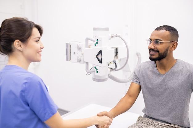 Homem intercultural jovem e feliz apertando a mão de seu médico ou enfermeira após tratamento médico e recuperação