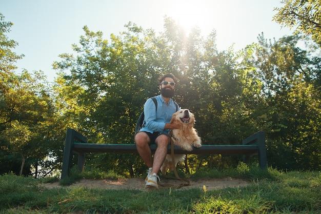 Homem interessante sentado com seu cachorro na cadeira no parque