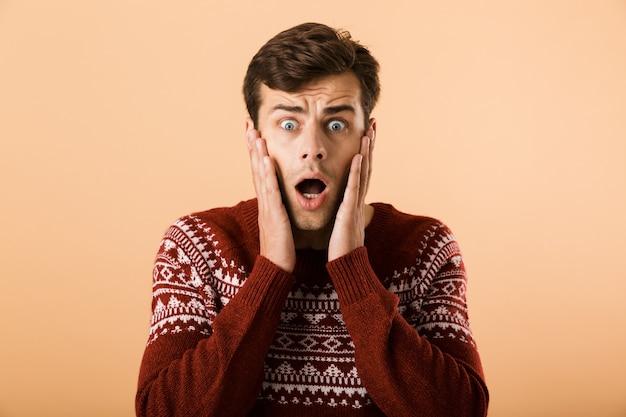 Homem intimidado com a barba por fazer, vestindo um suéter de tricô gritando e tocando o rosto, isolado sobre uma parede bege